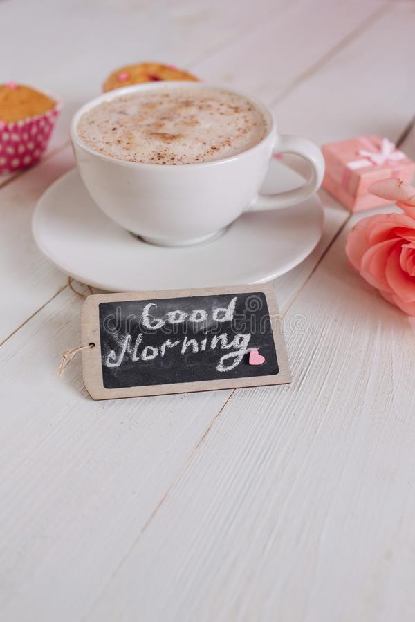 Caneca de café com bom dia do bolo, o cor-de-rosa e das notas na tabela rústica branca de cima de, café da manhã acolhedor e sabo foto de stock royalty free