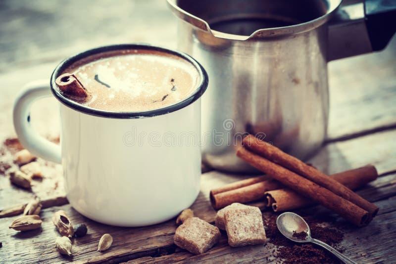Caneca de café com canela e o potenciômetro turco na tabela imagens de stock