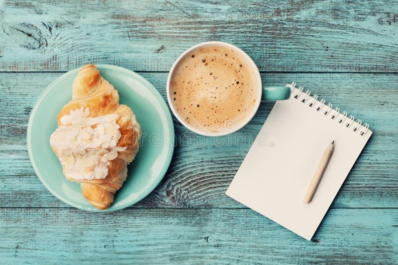 Caneca de café com croissant e caderno e lápis vazios para ideias do plano de negócios e do projeto na tabela rústica de turquesa fotografia de stock