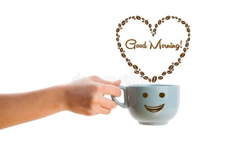 A caneca de café com feijões de café deu forma ao coração com sinal do bom dia foto de stock