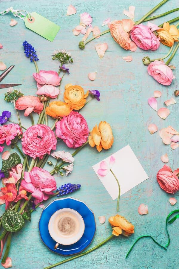 Caneca de café com o ramalhete de flores bonitas e do cartão de papel vazio no fundo rústico de turquesa Café da manhã festivo e  imagem de stock
