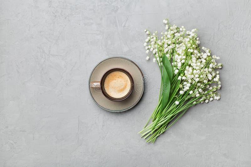 Caneca de café com o ramalhete do lírio das flores do vale na tabela de pedra cinzenta de cima na configuração do plano e do esti fotografia de stock