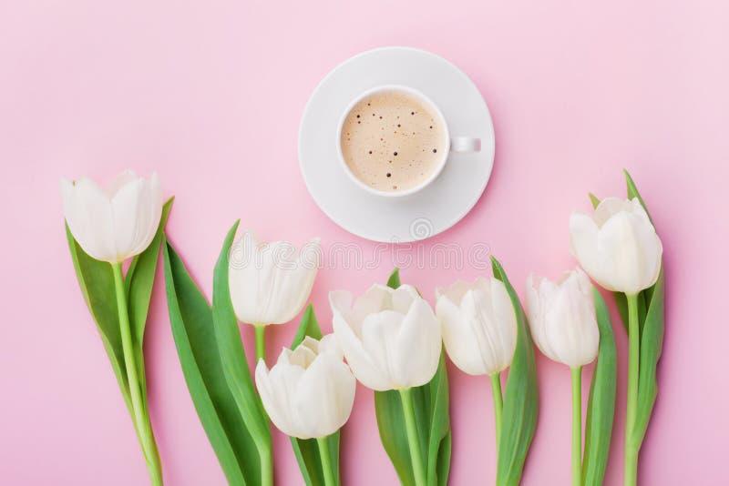 A caneca de café com tulipa da mola floresce para o bom dia na tabela cor-de-rosa acima no estilo da configuração do plano Café d imagem de stock royalty free