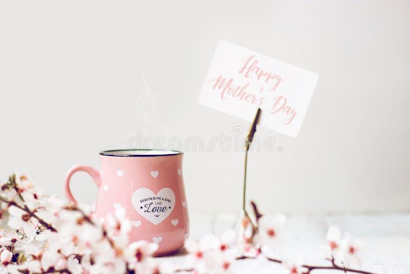 Caneca de café cor-de-rosa, flores brancas da cereja e 'nota do dia de mãe feliz ' imagem de stock royalty free