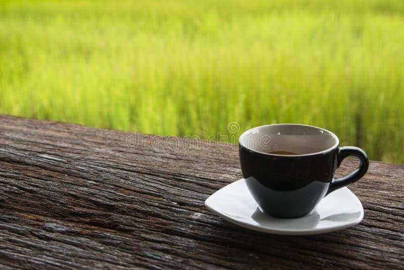 Caneca de café preto em de madeira fotografia de stock royalty free