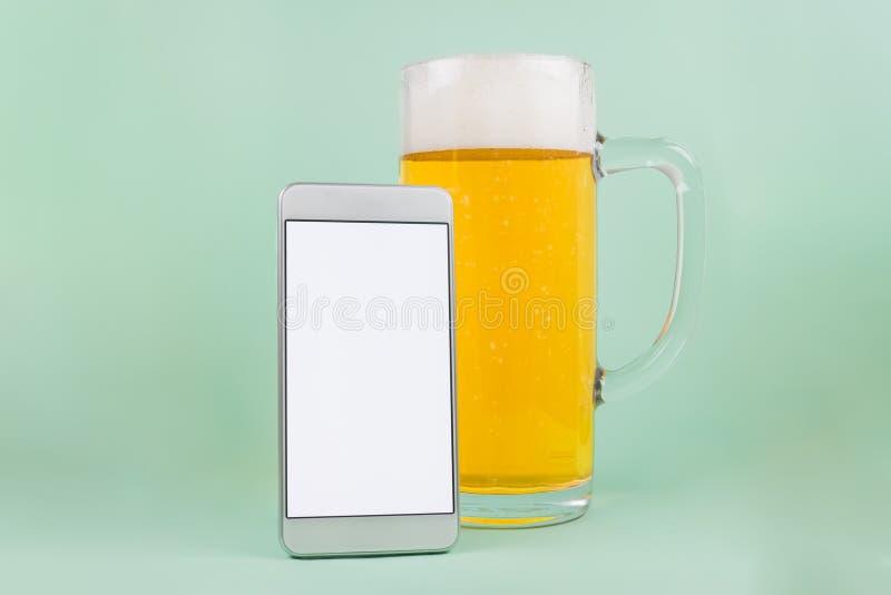 Caneca de cerveja com espuma e o smartphone branco da tela vazia Espaço para a cópia fotografia de stock royalty free