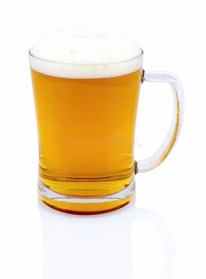 Caneca de cerveja com espuma no fundo branco com reflexão da sombra Metade um do litro da cerveja no vidro no contexto branco foto de stock