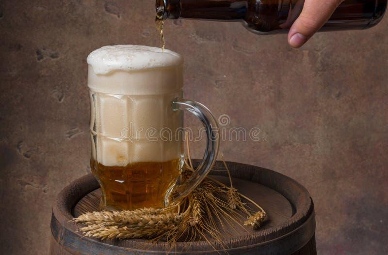 A caneca de cerveja com orelhas do trigo em um tambor de madeira e um fundo escuro muram, derramam a cerveja de uma garrafa fotografia de stock