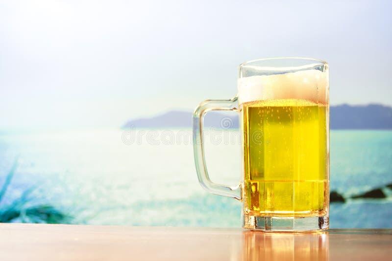 Caneca de cerveja de refrescamento na praia fotos de stock