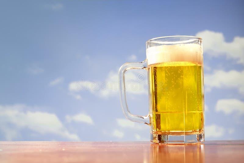 Caneca de cerveja de refrescamento no fundo do céu fotografia de stock royalty free