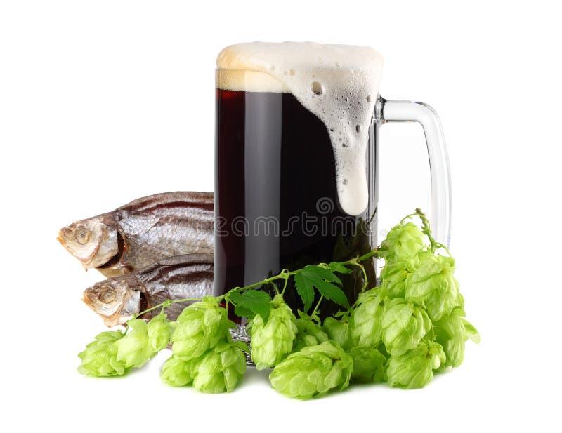 A caneca de cerveja escura com os cones secados dos peixes e do l?pulo isola-se no fundo branco Conceito da cervejaria da cerveja imagem de stock royalty free