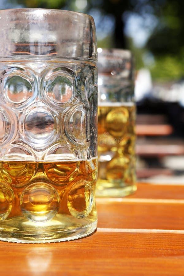 Caneca de cerveja meio cheia no jardim da cerveja imagem de stock royalty free