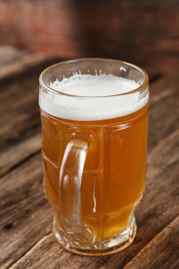 Caneca de cerveja no fundo de madeira escuro, fim acima fotografia de stock