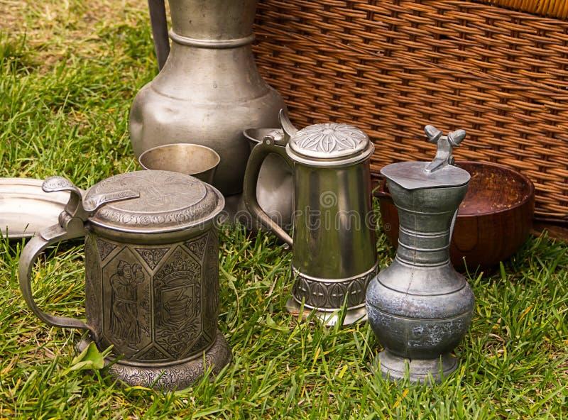 Caneca de cerveja velha metal a garrafa com piquenique velho cinzelado pinta do close-up da embarcação na grama imagens de stock royalty free