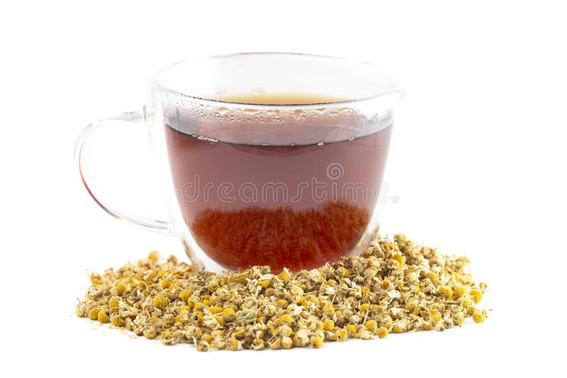 Caneca de chá de camomila quente com as flores secadas da camomila isoladas em um fundo branco fotografia de stock