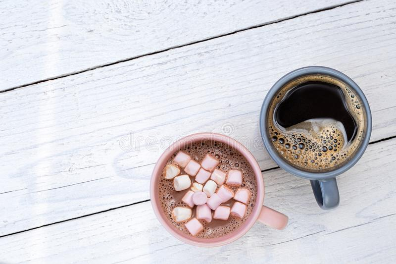 Caneca de chocolate quente com marshmallows pequenos ao lado de uma caneca de café preto isolada na madeira pintada branca de cim fotos de stock