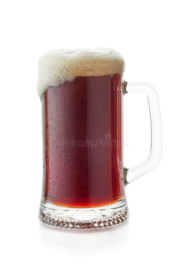 A caneca de fluxo do woth da cerveja escura espuma para baixo no branco fotografia de stock