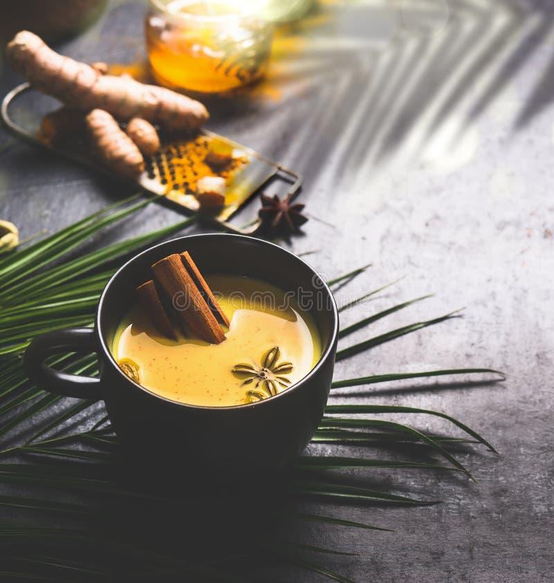 Caneca de leite dourado indiano da cúrcuma com as especiarias no fundo escuro com ingredientes fotos de stock royalty free