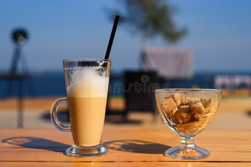 Caneca de vidro com latte e abanador e açucareiro de sal com açúcar de bastão na tabela de madeira fotografia de stock royalty free