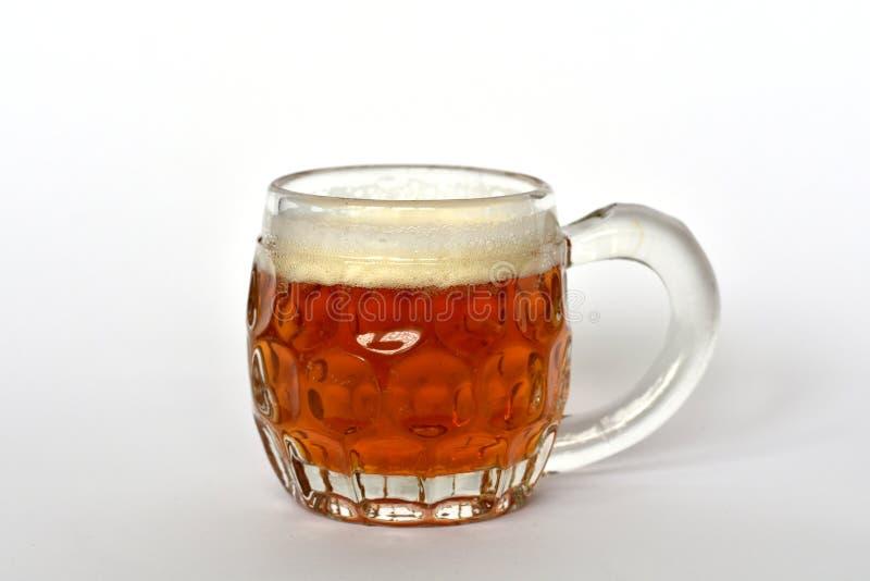 Caneca de vidro com punho completamente da cerveja dourada do ofício imagens de stock royalty free