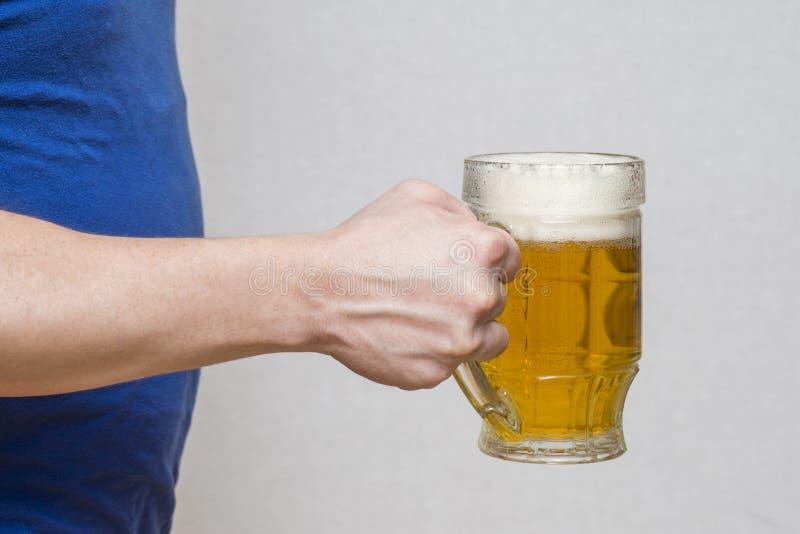 Caneca de vidro da posse da mão de cerveja no fundo branco Cerveja em uma terra arrendada de vidro à mão fotografia de stock