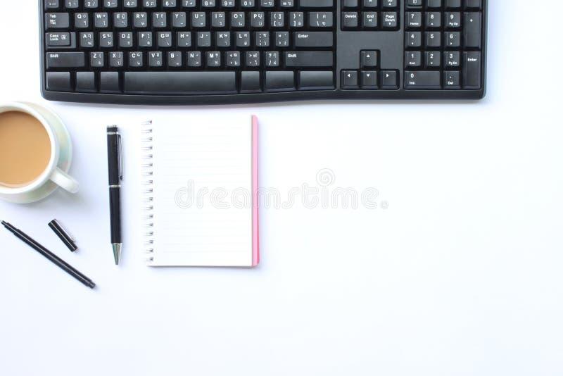 Caneca do caderno, da pena, do teclado e de café colocada em uma mesa branca em t imagens de stock royalty free