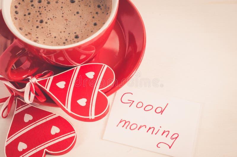 Caneca do cappuccino com bom dia de madeira do coração e das notas foto de stock