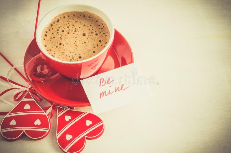 A caneca do cappuccino com coração de madeira e as notas sejam as minhas imagens de stock royalty free