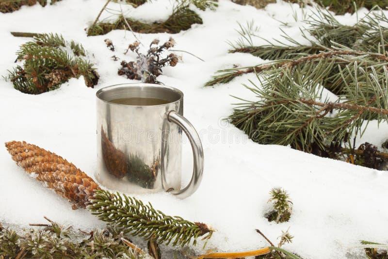 Caneca do metal de chá quente na neve Bebida quente em um dia gelado imagem de stock