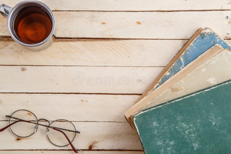 Caneca do vintage com os livros da bebida e do vintage no fundo de madeira Vista superior imagens de stock royalty free