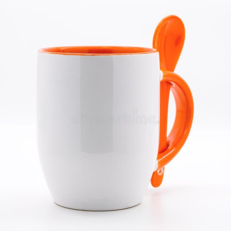 Caneca e colher alaranjadas de café em contextos brancos modernos Copo de ch? vazio para seu projeto imagens de stock royalty free