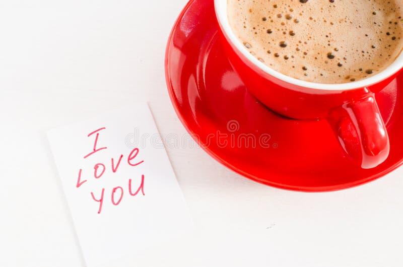 Caneca e notas do cappuccino eu te amo na tabela rústica clara imagens de stock