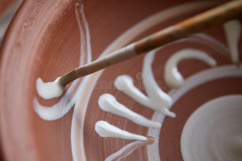 Caneca feito a mão semelhante em uma prateleira de madeira, close-up do oleiro da cara assustador, profundidade do shellow do cam imagem de stock