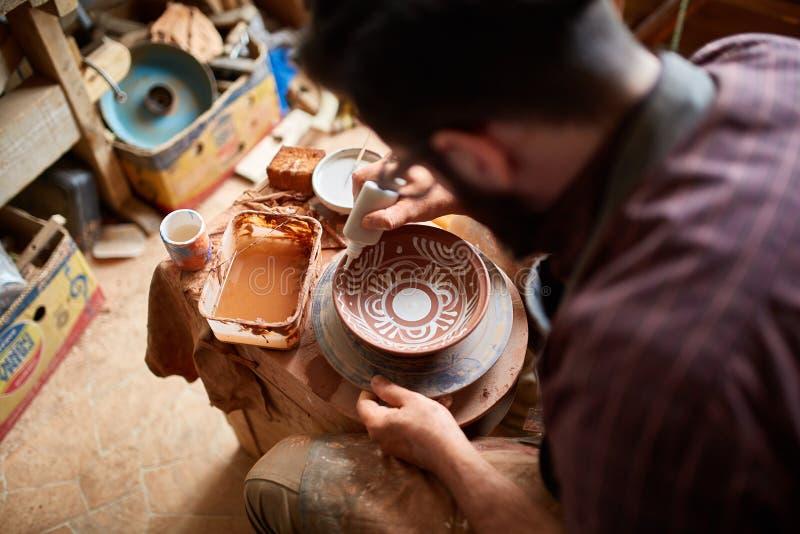 Caneca feito a mão semelhante em uma prateleira de madeira, close-up do oleiro da cara assustador, profundidade do shellow do cam fotos de stock