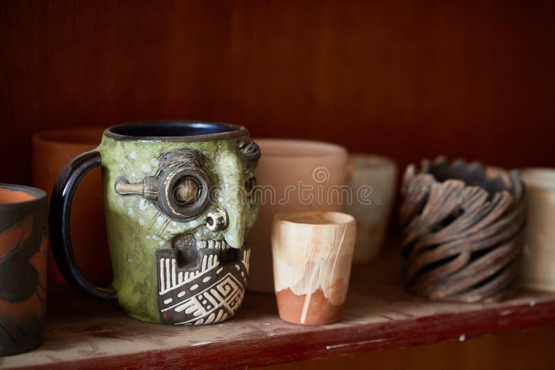 Caneca feito a mão semelhante em uma prateleira de madeira, close-up do oleiro da cara assustador, profundidade do shellow do cam imagens de stock royalty free