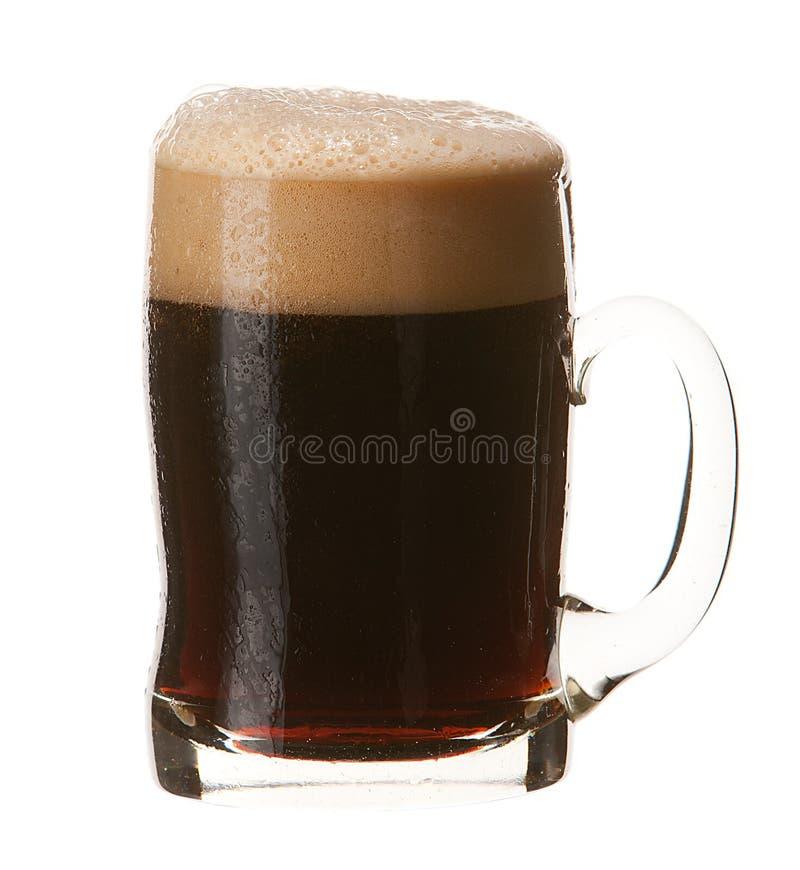 Caneca fria de cerveja escura com a espuma isolada no fundo branco fotografia de stock royalty free