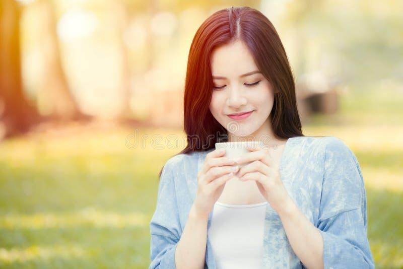 Caneca guardando adolescente da menina a beber o chá quente no sorriso da manhã do parque fotos de stock