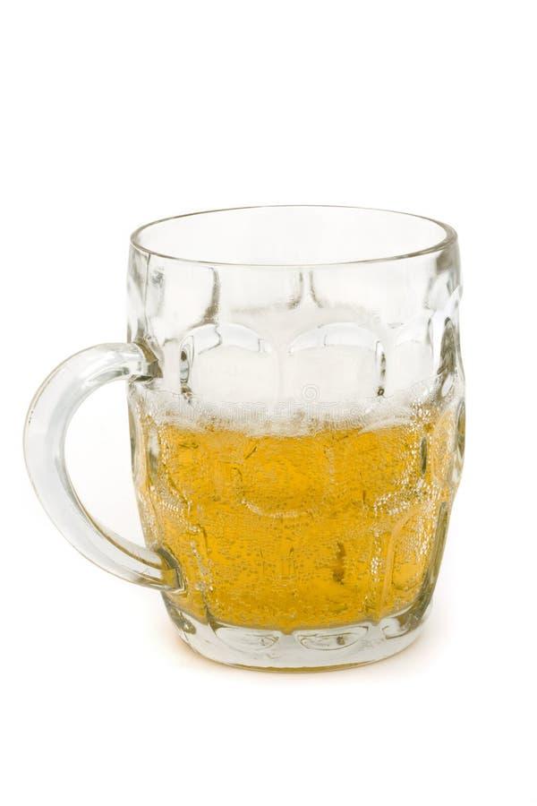 Caneca para cerveja de vidro meio cheia da cerveja sobre o branco fotografia de stock