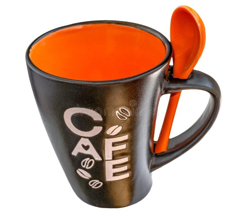 Caneca preta e alaranjada vazia da cerâmica de café com a colher alaranjada da cerâmica foto de stock