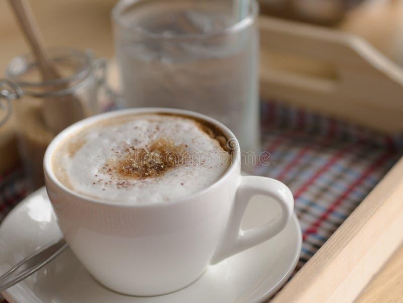 Caneca quente do cappuccino com cobertura branca do açúcar mascavado da espuma na água potável de copo branca no close up de vidr fotos de stock royalty free