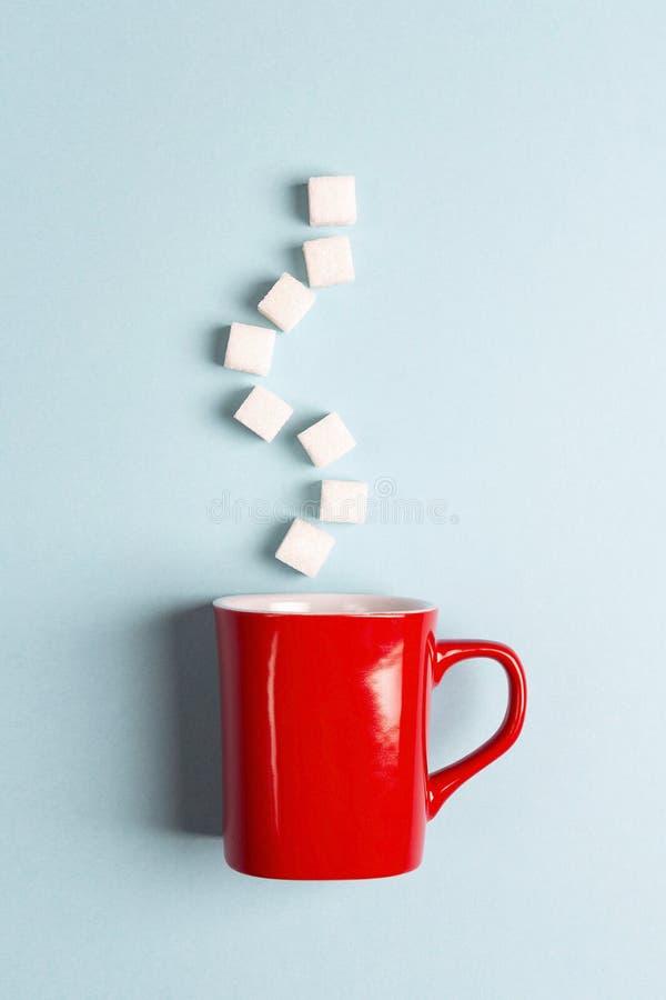 Caneca vermelha com cubos do açúcar em um fundo azul Sugar Addict imagem de stock royalty free