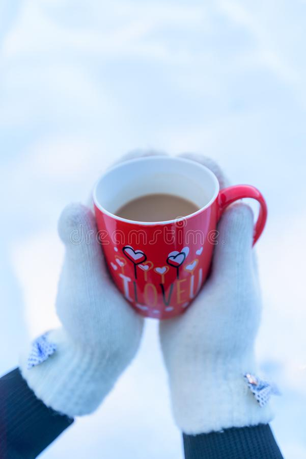 Caneca vermelha com a inscrição nas mãos de uma menina nos mitenes brancos Foto do inverno Dia do `s do Valentim fotos de stock