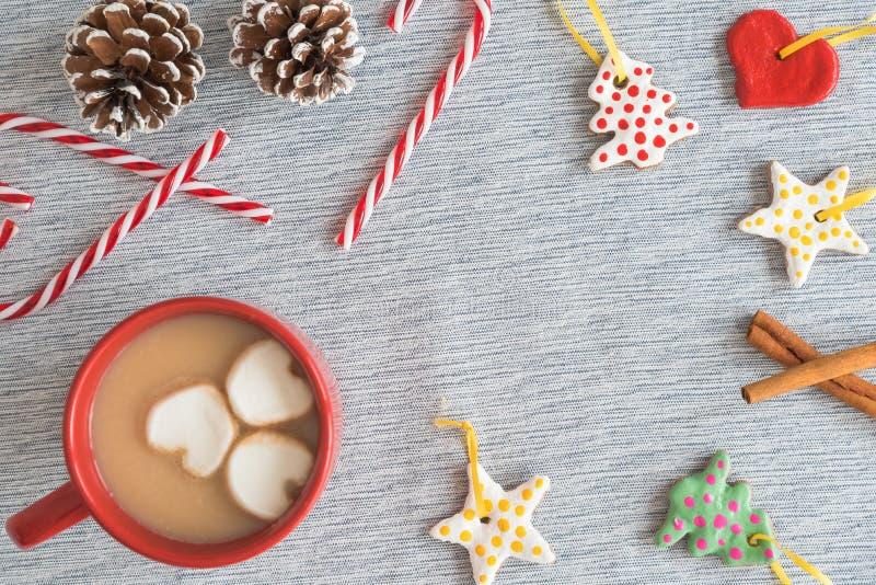 Caneca vermelha de cacau quente com quadro de ornamento feitos a mão do Natal, bastões de doces, pinecones fotos de stock