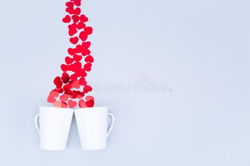Canecas brancas da porcelana com confetes do coração do brilho Engodo de Valentine Day fotografia de stock