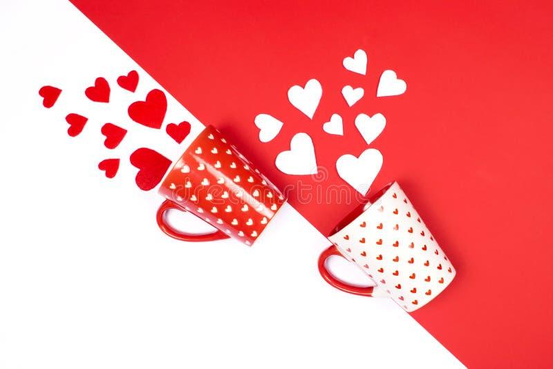 Canecas com corações dispersados em vermelho e em branco imagens de stock