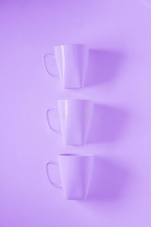 3 canecas de café roxas no fundo arroxeado em uma fileira vertical, espaço vazio da cópia foto de stock