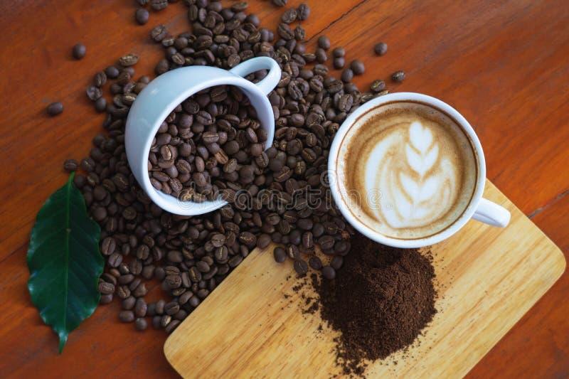 Canecas de caf? branco e feij?es de caf? derramados em uma tabela de madeira, arranjado belamente, decorada com folhas do caf? ?  fotos de stock royalty free