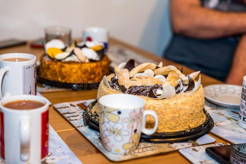 Canecas dos copos de chá com as duas galdérias do bolo da sobremesa na tabela de madeira em casa fotografia de stock royalty free