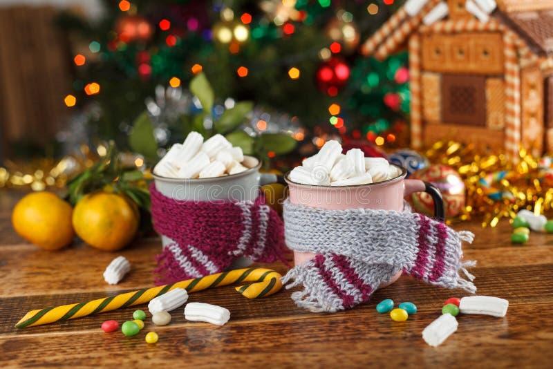 Canecas nos scarves com os marshmallows quentes e os doces de uma bebida Ainda vida festiva imagens de stock