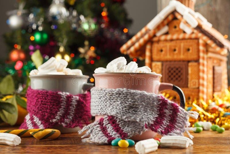 Canecas nos scarves com os marshmallows quentes e os doces de uma bebida no fundo de uma casa de pão-de-espécie Ainda vida festiv fotos de stock